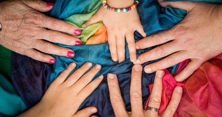 Fünf Hände - jung und alt - berühren sich auf einem bunten Seidentuch.